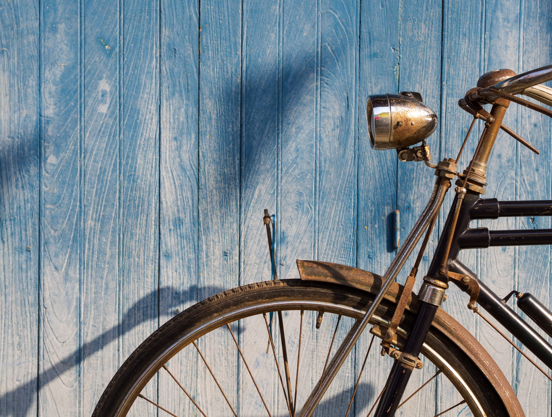 Old bicycle parked in front of blue plank floor for text and background.