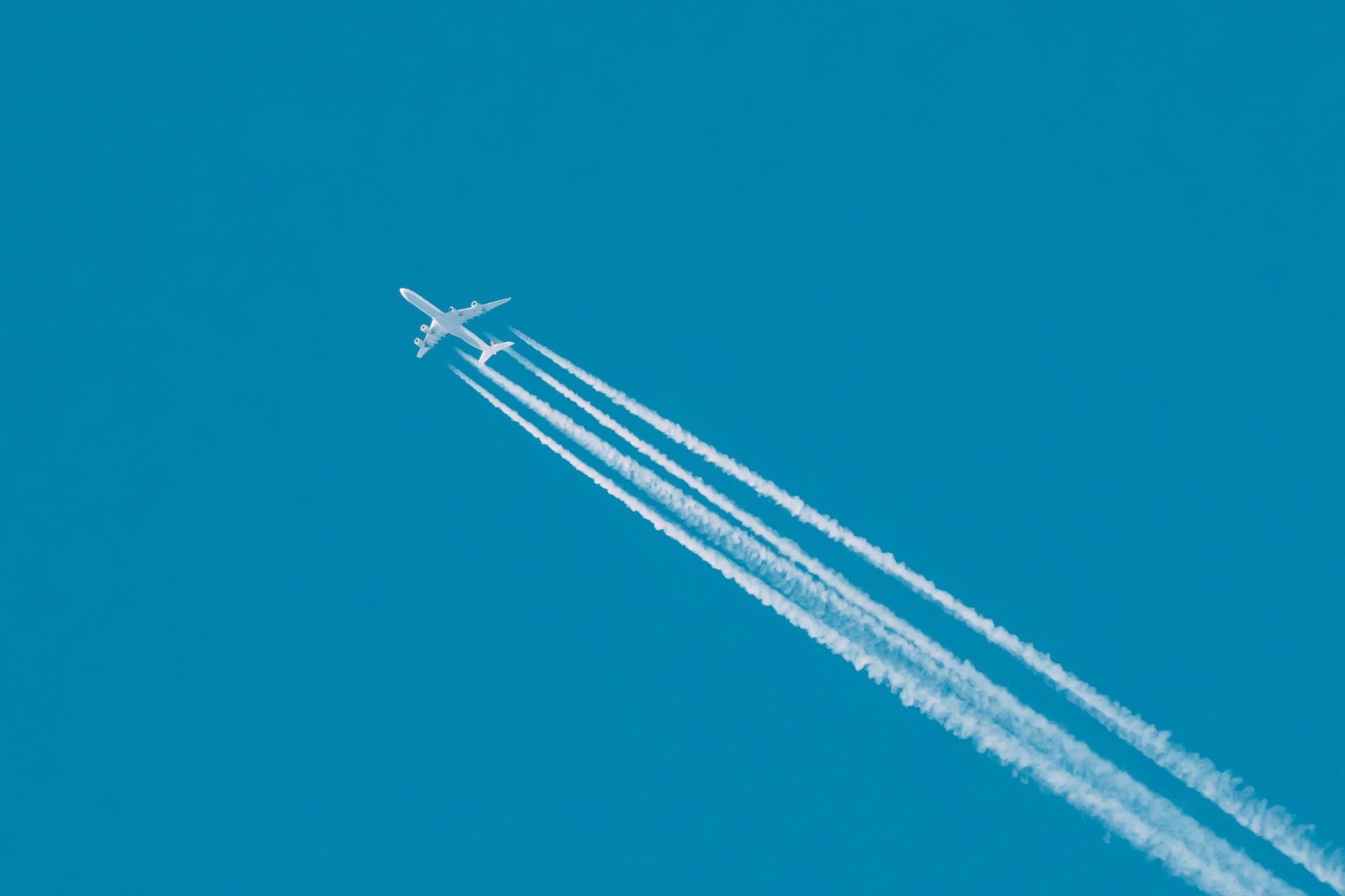 Contrail In Blue Sky. Plane, Clear Sunny Sky Background. Airplane Aircraft In Sky With Plane Trails